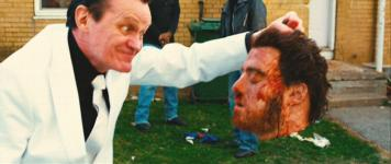 Brian Downey holding Robb Wells' severed head in 'Hobo with a Shotgun'